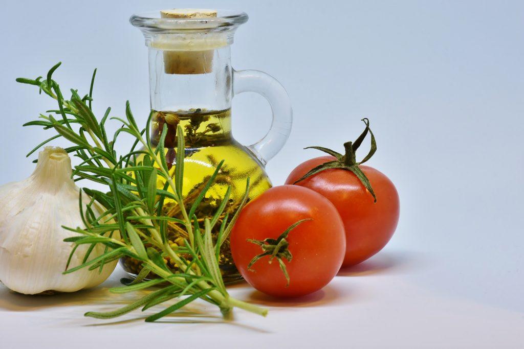 Petite bouteille d'huile d'olive entourée de deux tomates, d'une gousse d'ail et d'un aromate